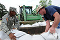 Defense.gov News Photo 110509-F-LH943-944 - A U.S. soldier left serving with the 77th Aviation Brigade of the Arkansas Army National Guard assists in the filling and placing of sandbags in.jpg