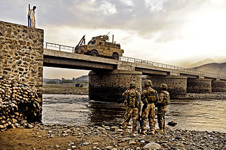 Laghman Province - Members of the U.S. Air Force inspecting the underside a bridge as traffic squeezes through the narrow roadway in Mihtarlam.