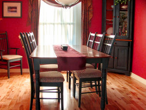 A dinner table with wooden chairs in a living ...