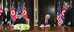 Donald Trump and Kim Jong-un seated at a table