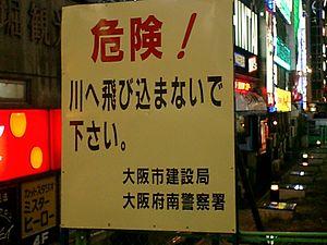 "Curse of the Colonel - ""Dangerous! Do not dive into this river. Osaka Regional Development Bureau and Osaka-Minami Police station"" sign at Ebisubashi bridge"
