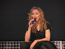 Madonna sitting down and singing, her eyes are closed.