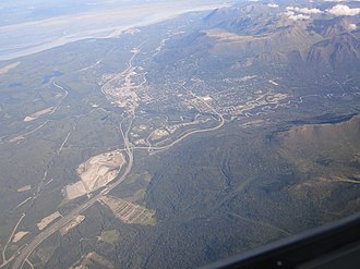 Eagle River, Anchorage - Aerial view, looking northeasterly, of Eagle River and the surrounding area.  View includes portions of Chugach State Park, the Glenn Highway, Joint Base Elmendorf-Richardson and Knik Arm. The river of Eagle River itself can be seen following a winding path to the south of the settlement.