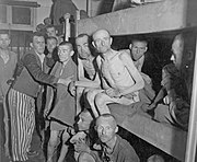 A group of malnutrished prisoners, some of them naked, some dressed in prisoner clothing, fill the interior of one of the barracks, as well as two lower levels of a three-storey bed.