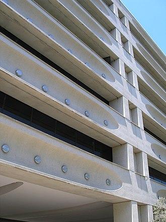Edmund Barton Building - Facade of the Edmund Barton Building, showing facade beams and stainless steel caps covering concrete prestressing anchorages.