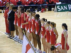 English national team is standing in a row, wearing red uniforms, on one of the centre lines that divides the court in three.