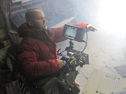 Here, young director William Eubank performs multiple roles as on-set director and camera operator. - Film director