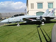 A twin-tailed jet fighter is posed on the lawn.