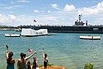 Families wave as USS John C. Stennis renders honors to the USS Arizona Memorial. (27966184886).jpg