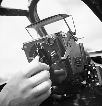 Gyro gunsight - The instrument panel of a Spitfire IX  showing the Mk IID Gyro reflector gunsight. To set range the dial adjusts the reticle size to match target wingspan. Currently set to the Junkers Ju 88, it ranged in size from the large Fw 200 Condor to the small Messerschmitt Bf 109.