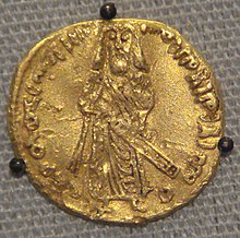 Coin with protruded inscription in Arabic and a bearded man standing with sheathed sword, seen face-on