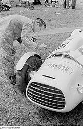 Černobílá fotografie Škody Supersport v depu. Vedle stojící mechanik štětcem maluje startovní číslo na bok vozu.