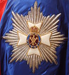 The embroidered star of an English order of Knighthood, with radiating silver rays, topped with a white Maltese cross and royal cypher in the centre