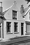 Huis met gepleisterd tuitgeveltje aan de straat, schuifvensters voordeur met bovenlicht