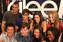 "A group of people huddled together, with the backdrop displaying the word ""Glee"" in white small fonts."
