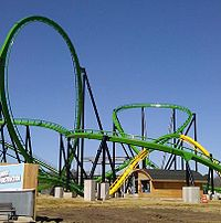 Green-and-yellow roller-coaster track against blue sky