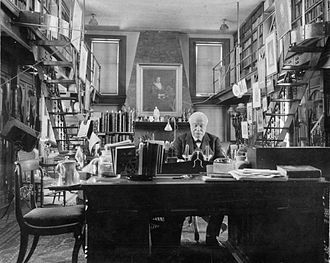 """Daniel Pabst - Horace Howard Furness in his library at """"Lindenshade,"""" Wallingford, Pennsylvania, ca. 1900. The Furness-Pabst bookcases are beneath the balcony at far right and far left. The lamps of the Furness-Pabst desk (now at the Philadelphia Museum of Art) are visible in the background, right."""