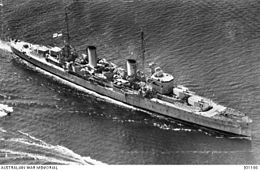 Three-quarter overhead view of cruiser with twin funnels and four gun turrets, at sea