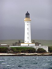 A tall white lighthouse with a brown stripe around the parapet and dark coloured lantern sits on a rocky shore. A white wall obscures the lower floor of grey stone buildings gathered around its base.