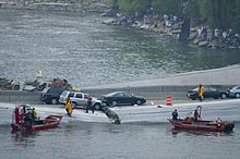 Emergency personnel running on the collapsed bridge and two Minneapolis Fire Department boats in the water with dozens of observers on the bank of the Mississippi