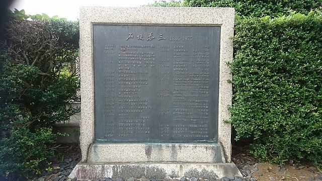 墓の横にある石碑には、泰三の功績が年表で記されている Wikipediaより