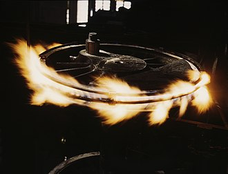 Train wheel - Steel tire on a steam locomotive's driving wheel is heated with gas flames to expand and loosen it so it may be slipped over the wheel.