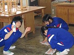 Murid sekolah sedang mengepel lantai