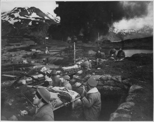"U.S. Marines observing the battle from trench positions, June 3, 1942 Japanese attack on Dutch Harbor, June 3, 1942. Group of Marines on the ""alert"" between attacks. Smoke from burning... - NARA - 520589.tif"