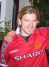 A photograph of a man with medium-length dirty blonde hair wearing a red shirt.