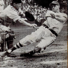 A black-and-white photo of a man wearing a baseball uniform sliding feet-first into home plate