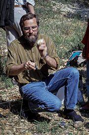 Photographie en couleur d'un homme à demi accroupi, portant une barbe et des lunettes et vêtu d'un jean et d'une chemise marron en train de reconstituer un débitage laminaire par percussion directe.