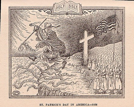 "In this 1926 cartoon, the Ku Klux Klan chases the Roman Catholic Church, personified by St. Patrick, from the shores of America. Among the ""snakes"" are various supposed negative attributes of the Church, including superstition, the union of church and state, control of public schools, and intolerance. KKK - St Patricks Dau (cr).jpg"