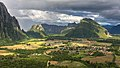 Karst peaks and green paddy fields under a stormy sky, South view from Mount Nam Xay, Vang Vieng, Laos.jpg
