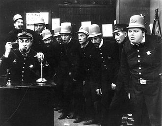 "Keystone Cops - The Keystone Cops in a typical pose in In the Clutches of the Gang (1914). The desk officer using the telephone is Ford Sterling. The policeman directly behind Sterling (in extreme background, left) is Edgar Kennedy. The young cop to Kennedy's left is Robert Cox. The hefty policeman at extreme right is Roscoe ""Fatty"" Arbuckle. The young constable with bulging eyes, fourth from right, is Arbuckle's nephew Al St. John. The casting of the Keystone police force changed from one film to the next; many of the individual members were per diem actors who remain unidentifiable."
