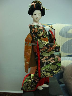A Japanese doll in kimono with fan.