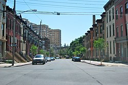 A view down a city street from an intersection. On either side are rows of two-story brick houses, largely identical with their neighbors. In the background a taller building is visible to the left.
