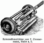 Rear quarter view of push mower mechanism showing fixed cutting blade in front of roller and wheel-driven (through gears) rotary blades
