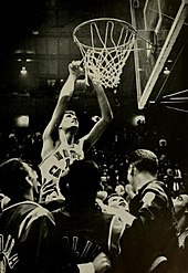 A basketball player cutting a net away from the rim.