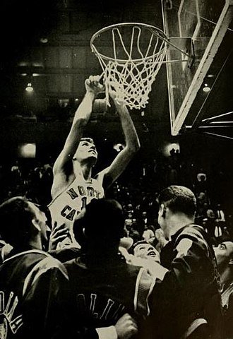 North Carolina Tar Heels men's basketball - The Tar Heels' Lennie Rosenbluth cuts down the nets after winning the 1957 title.