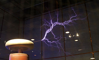 Streamer discharge - Streamer discharges into the air from the high voltage terminal of a large Tesla coil.  The streamers form at the end of a pointed rod projecting from the terminal.  The high electric field at the pointed end causes the air to ionize there.