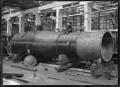 Locomotive boiler in the Petone Railway Workshops, with William Albert Godber sitting on top ATLIB 274438.png