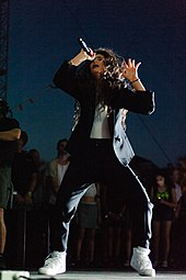 Lorde performing onstage with spontaneous and unchoreographed moves, wearing a blazer and white sneakers