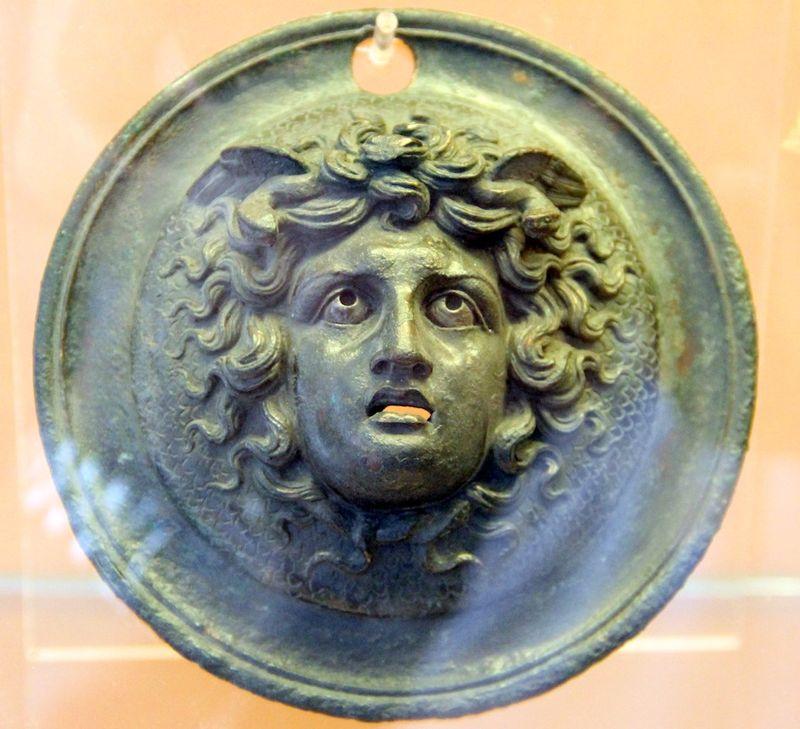 Dans un cercle, tête de Méduse entourée de cheveux, avec des serpents à la base du cou et des ailes en arrière de la tête. Bouche grande ouverte, yeux globuleux.