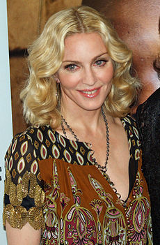 The bust image of a middle-aged blond woman with deep-blue eyes. Her hair is parted from the middle and falls in waves upto her neck. She appears to be wearing a brwon and black printed dress with the front open. A black chain is wound around her neck. She is looking slightly towards the right of the image and smiling.