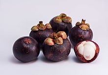 Photograph of several purple mangosteen fruits. One has been partially peeled revealing white flesh divided into five sections.