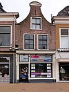 foto van Huis met ingezwenkte halsgevel met halfrond afgedekte top en met gewijzigde onderpui