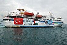 Photo d'un yacht de croisière blanc, orné de bannières de la Turquie et de la Palestine