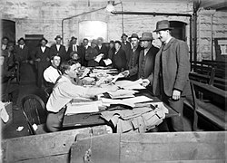 Men in suits and hats file past other men sitting at a long table, handing over paperwork