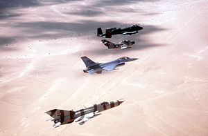 Operation Bright Star - Aircraft in flight over the desert during exercise Bright Star '82. The aircraft are from front to back: a MiG-21PFM, F-16 Fighting Falcon, MiG-15UTI and an A-10 Thunderbolt II