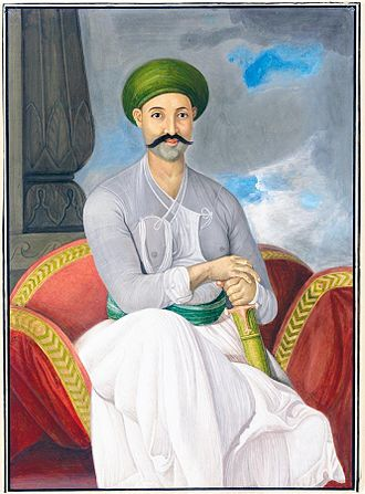 "Mirza Jawan Bakht - ""A Portrait of Prince Mirza Javan Bakht, Company School, Lucknow, India, circa 1786; watercolour and gouache on card, with a seated figure dressed in white with green waist sash and turban, holding a sheathed sword, unframed; inscriptions: in ink on the reverse in Urdu: 'the likeness of Mirza Jewan Bakht"""